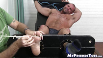 Tattooed hunk receives feet licking while masturbating